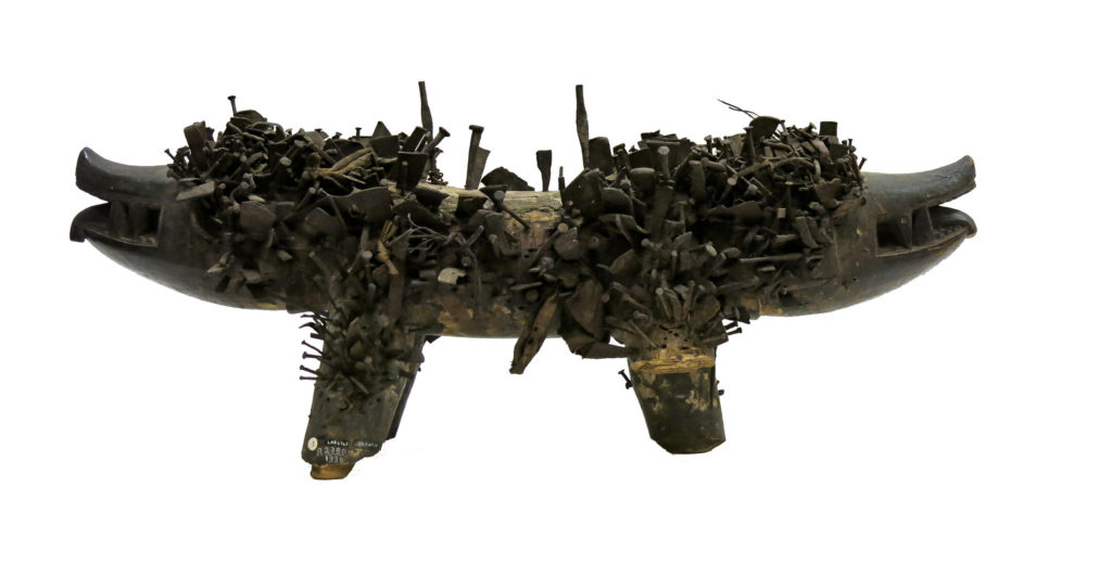 two headed dog figure with many nails sticking out