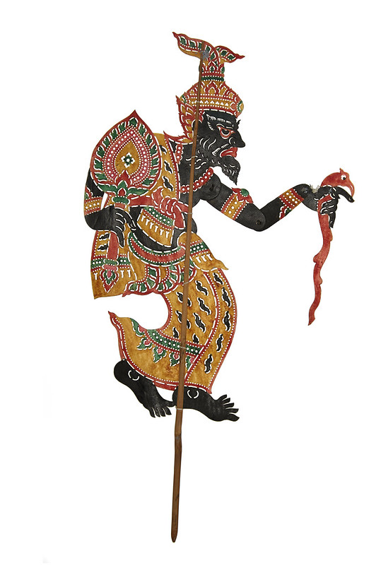 a shadow puppet with decorative clothing holding a fan and staff
