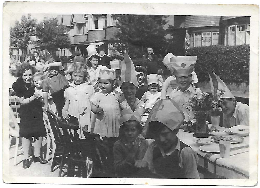 a photo of a VE Day street party with kids around a table