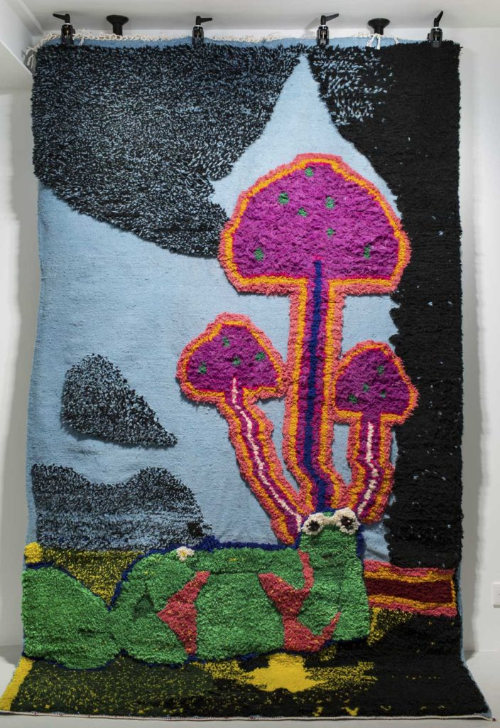 an embrodered artwork featuring magic mushrooms
