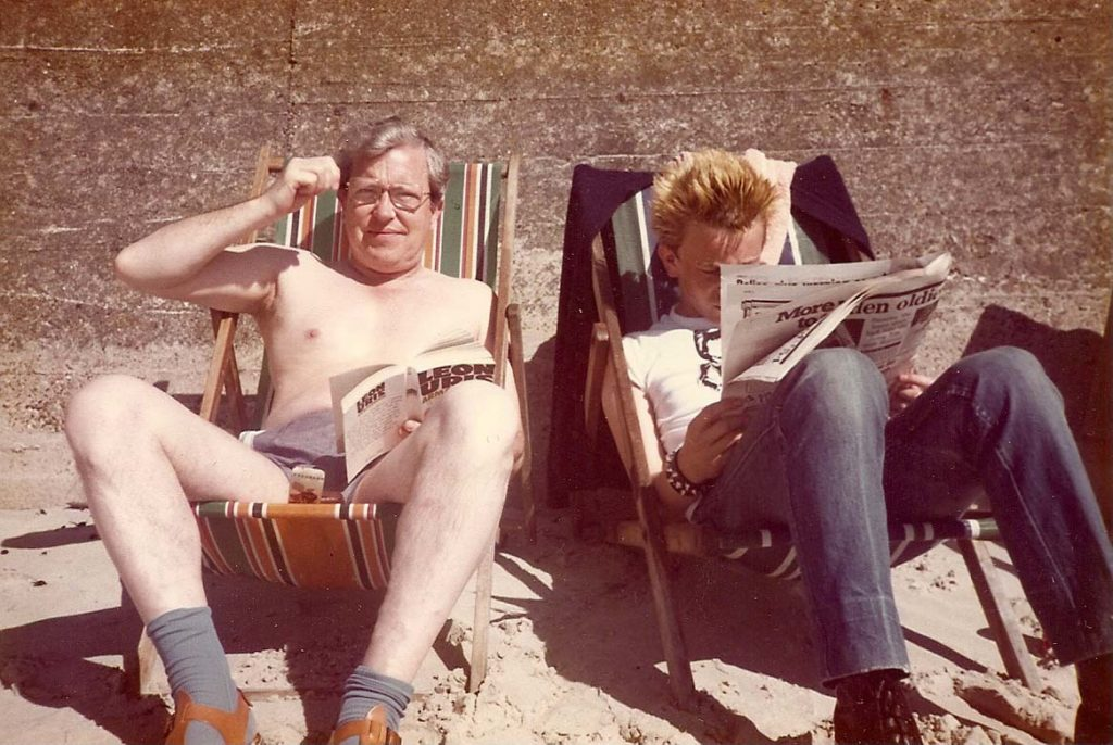 colour snap of a dad in socks and sandals sunbathing in deckchair as his son in punky dear reads a paper next to him