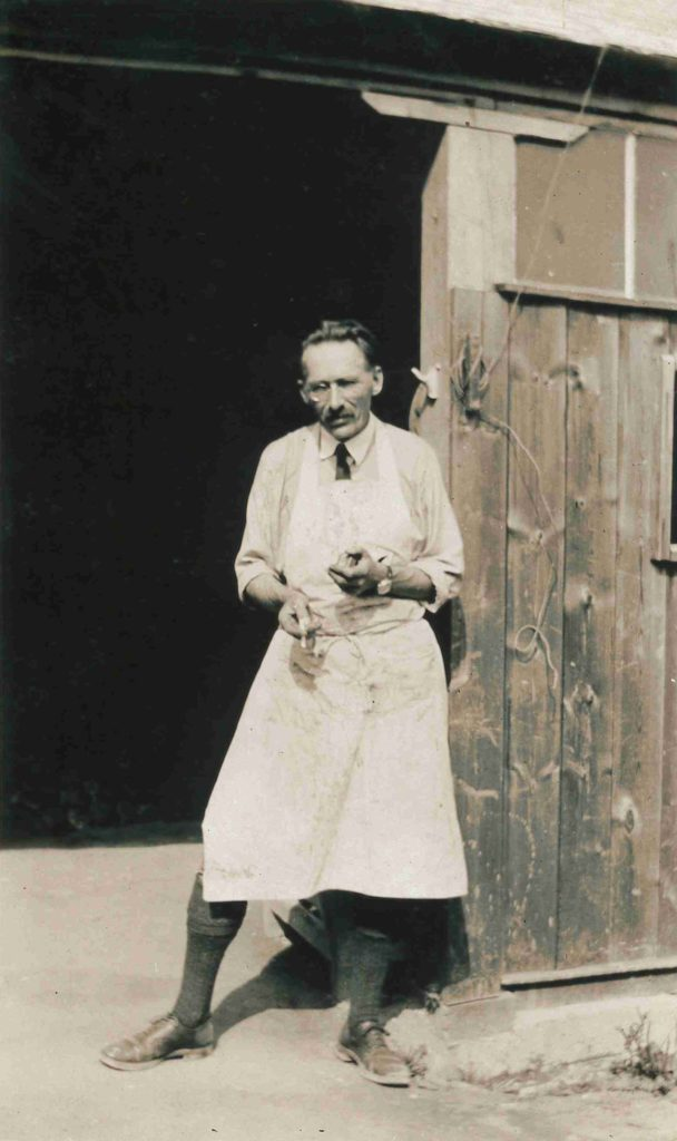 photo of a man in a apron by a barn door