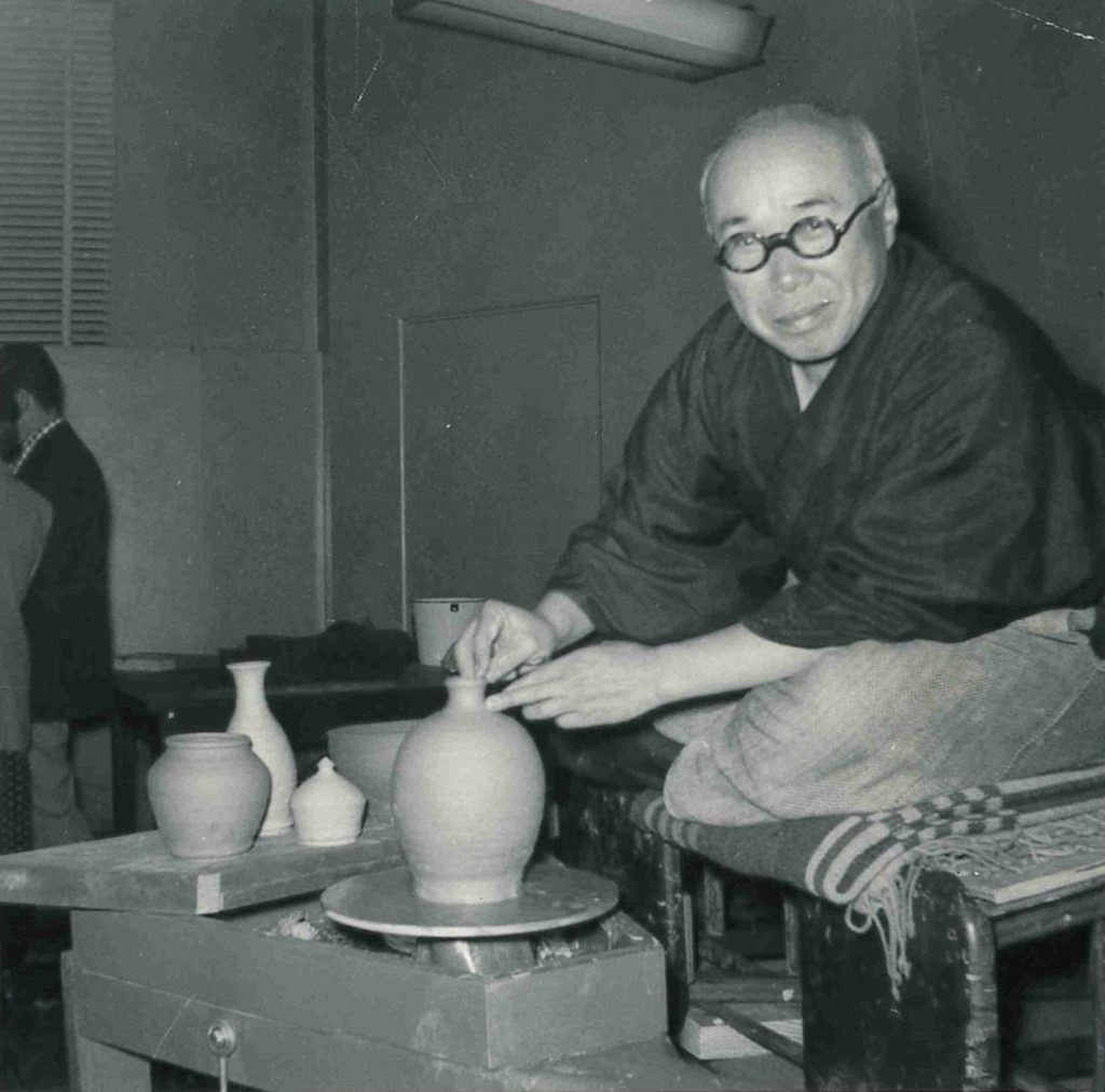 black and white photo of a man throwing a pot