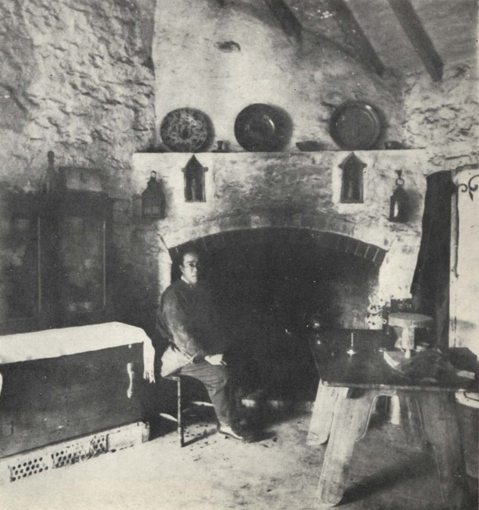 black and white photo of a man seated before a large fireplace