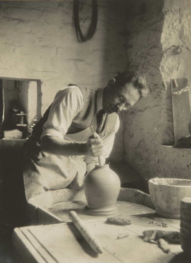black and white photo of a chap working on a pot