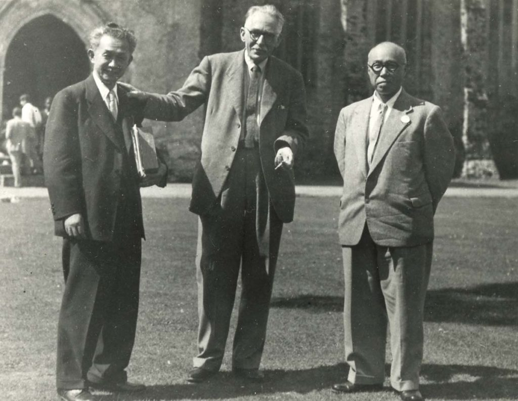 a photo of three men in suits on a lawn