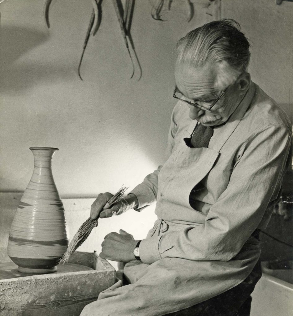 black and white photo of a man working a potters wheel