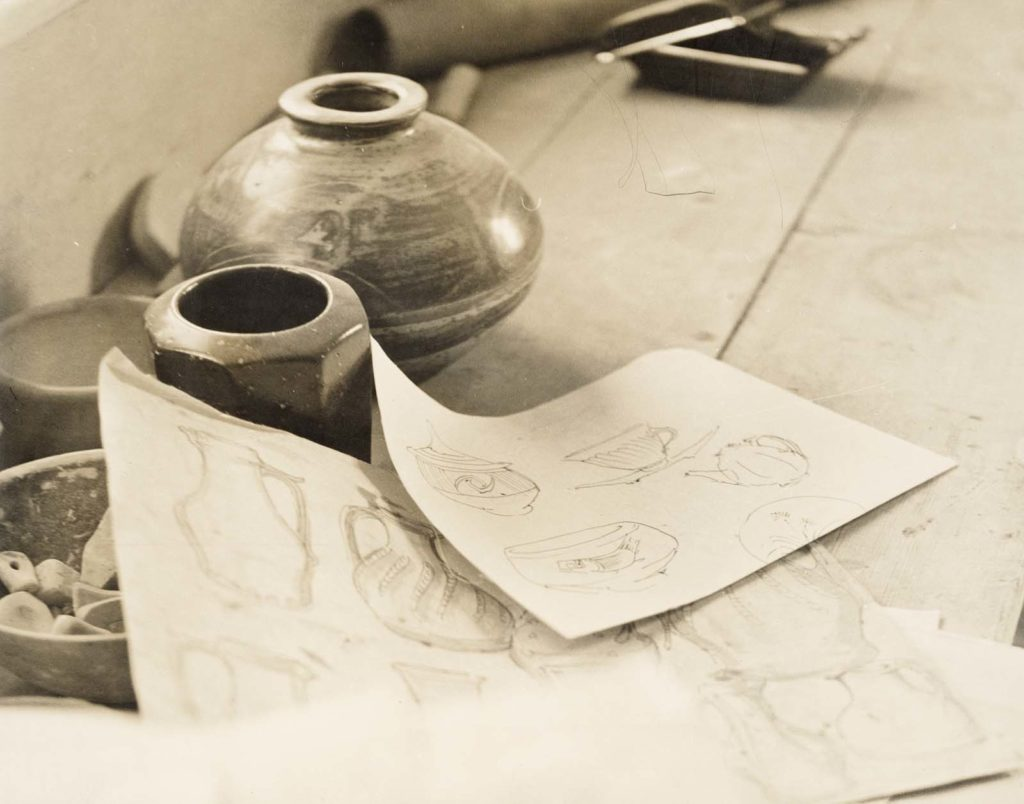 a photo of two pots and sketches on paper