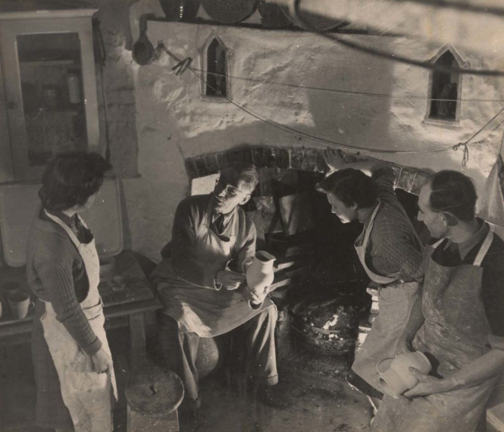 a black and white photo of a man before a fireplace holding a pot talking to three interested potters wearing aprons