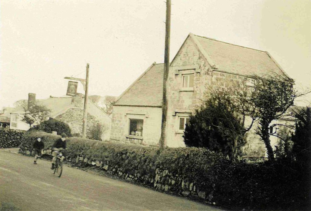 black and white photo of tow boys on bicycles passing a stone house on a country lane