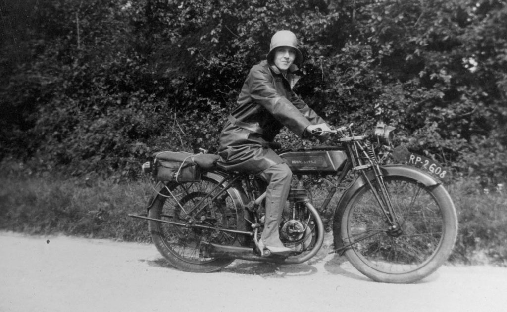 black and white photo of a woman with a 1920s flapper hat, high heels and leathers on a motorbike