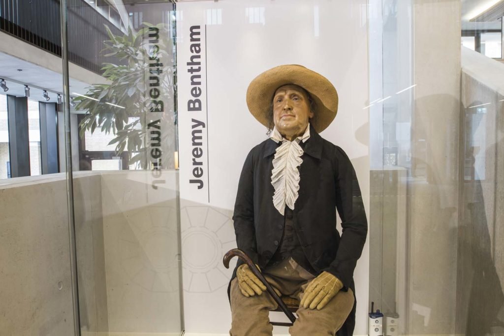 photo of a Jeremy Bentham's skeleton dressed in period clothes and wax head and hat in a case by an entrance stairway