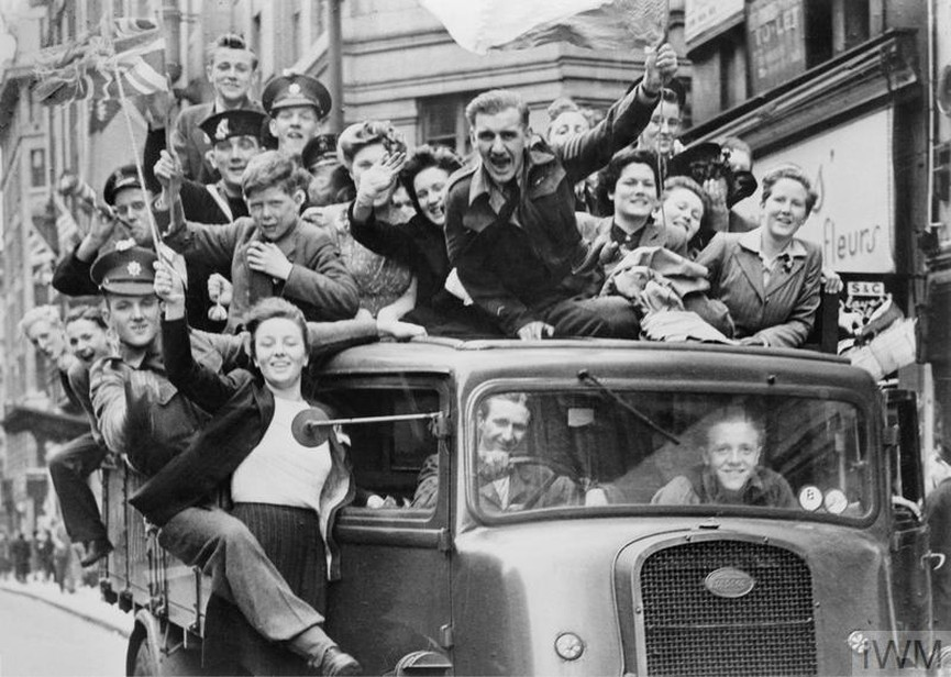 photo of cheering civilians and servicemen crowded onto a truck