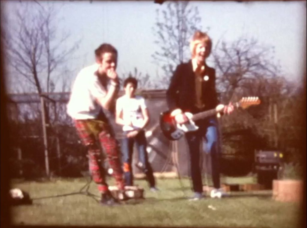 bluured photo of a bunch of young punk kids playing in a band outside