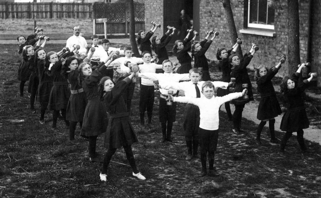 black and white photo of schooldchildren exercising a yard with weights