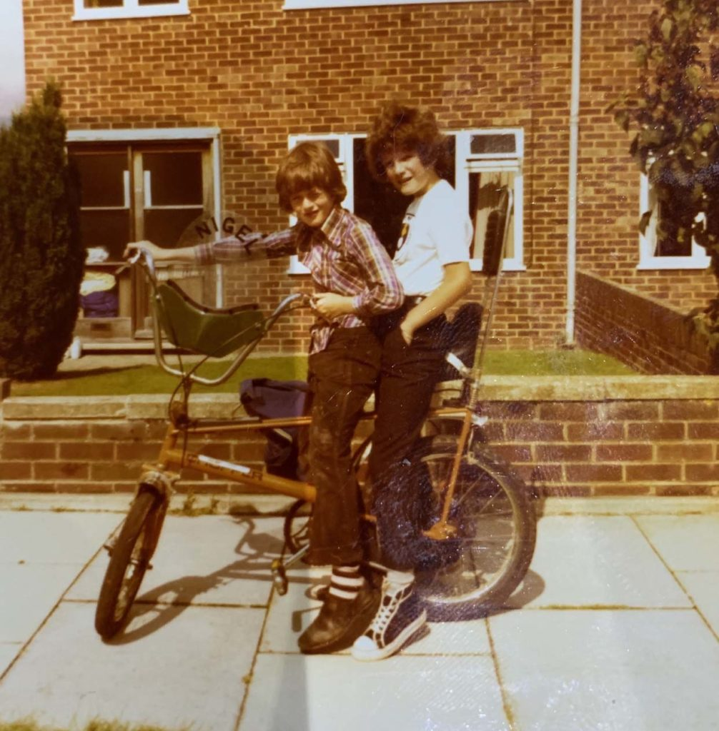 colour snap of two kids with flares on a chopper bike