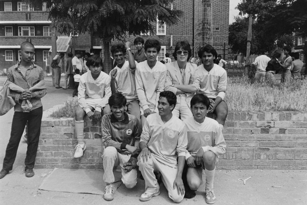 a photo of a group of young Asian teenagers posing for a group shot at a school