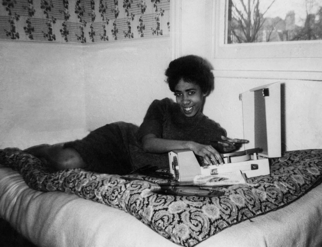 a black and white photo of a young black woman on her bed with a portable record player