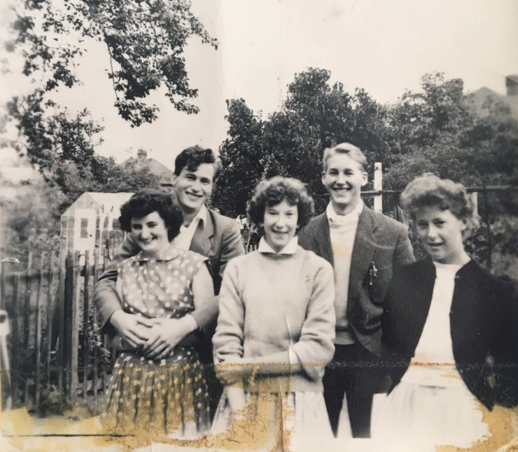 black and white photo of young white kids from the 1950s in jackets and woolens