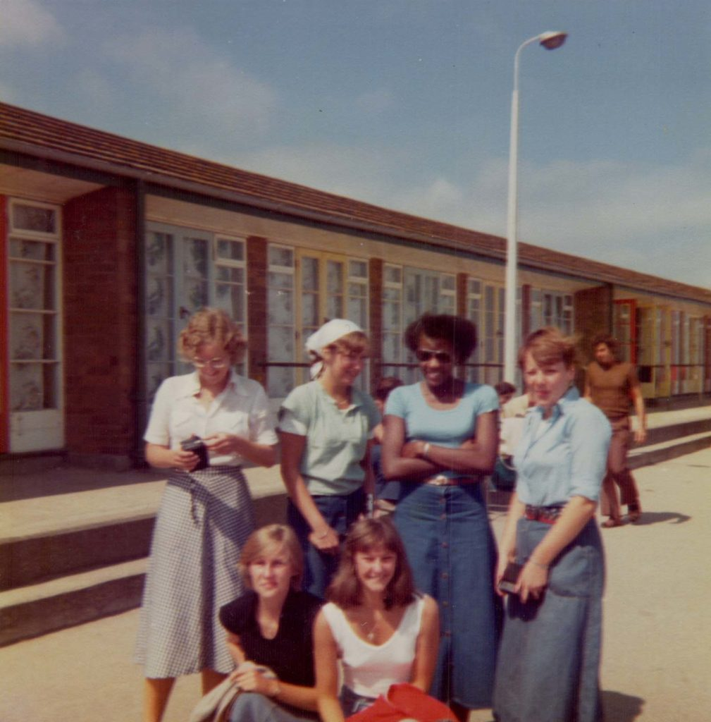 a photo of a group of young women posing for a photograph at a holiday camp