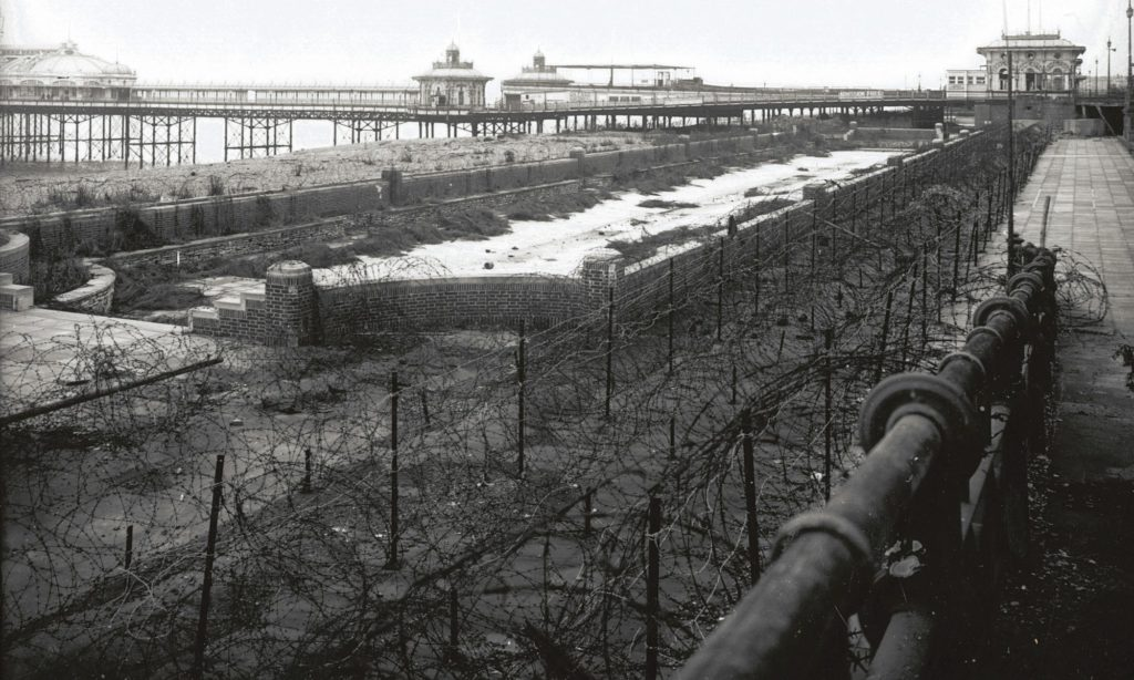 photo of a seafront and peer with barbed wire