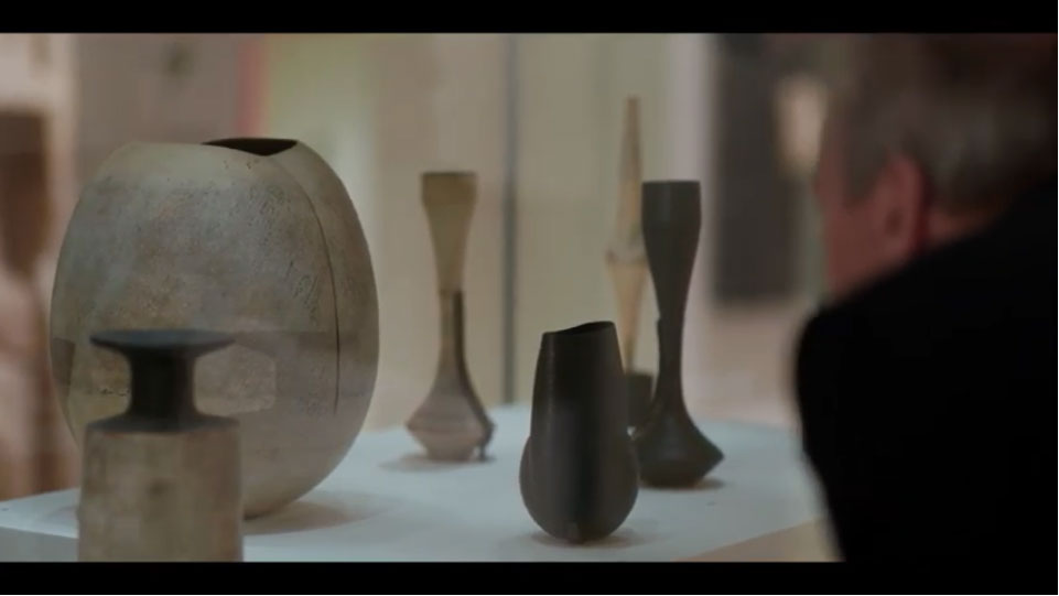 screenshot of video showing man looking at decorative pots through glass