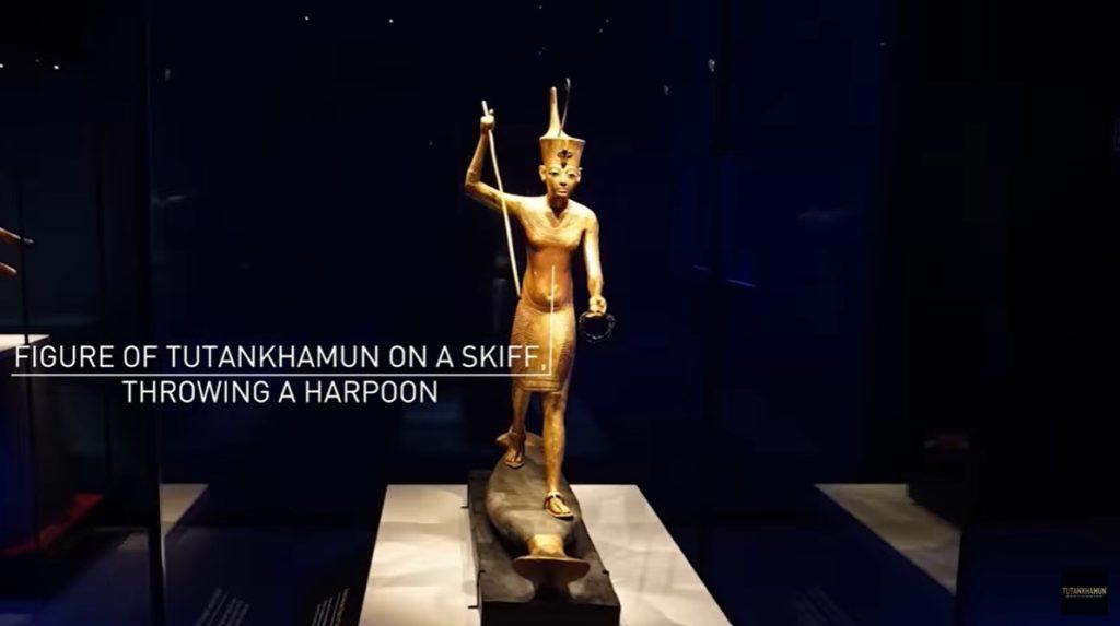 still of video walkthrough of Tutankhamun exhibition showing small golden figure of Tutankhamun on a skiff with a harpoon