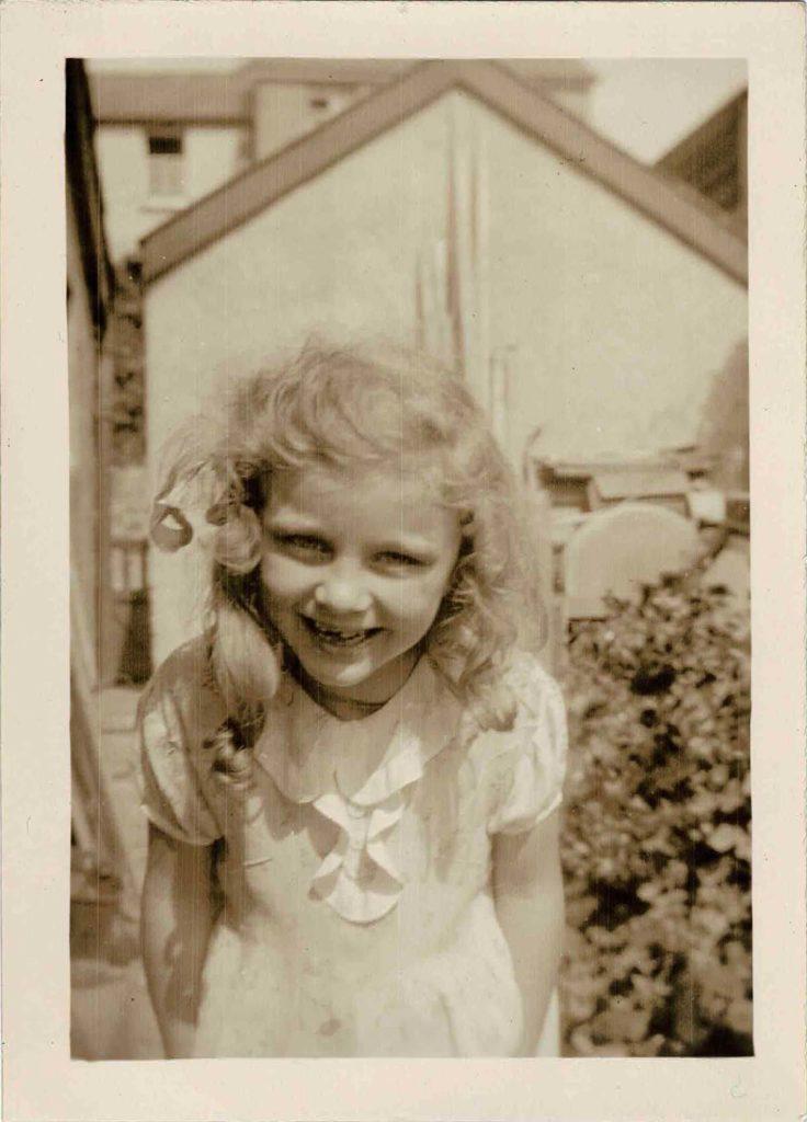 Photograph of Molly Coombe as a young girl in a garden