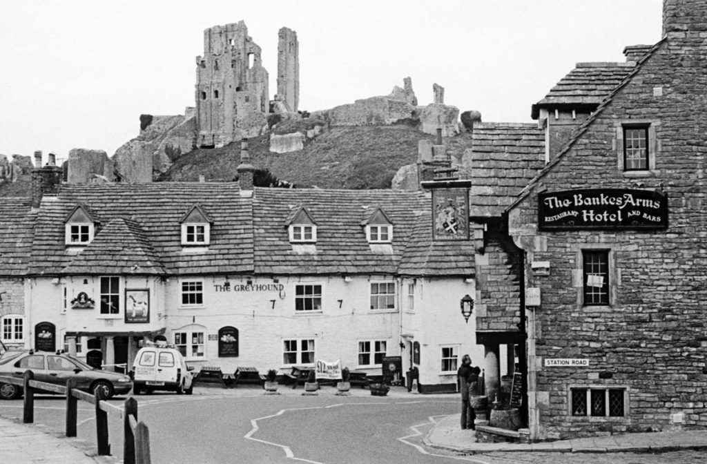 black and white photo of a village pub with a ruined castle on the hill behind