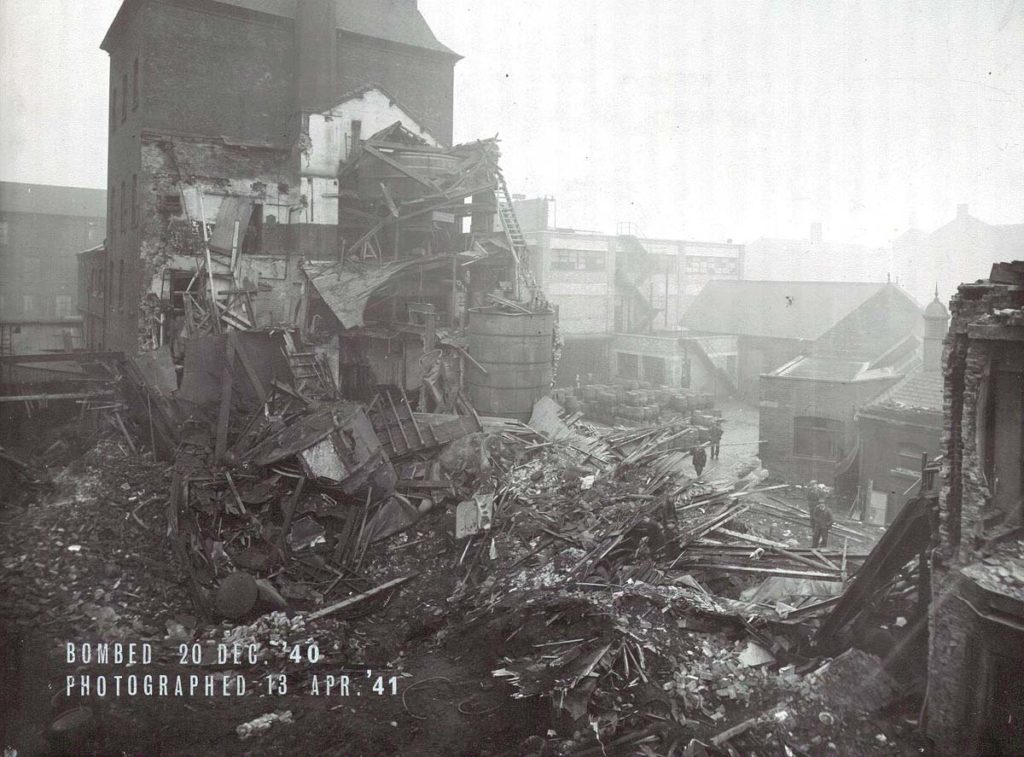 a photo of a bombed brewery building with men in the distance stacking barrels beyond the smoking ruins