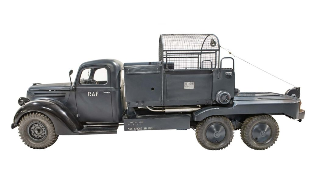 Six-wheeled dark grey metal vehicle with wire cage behind the driver's cab
