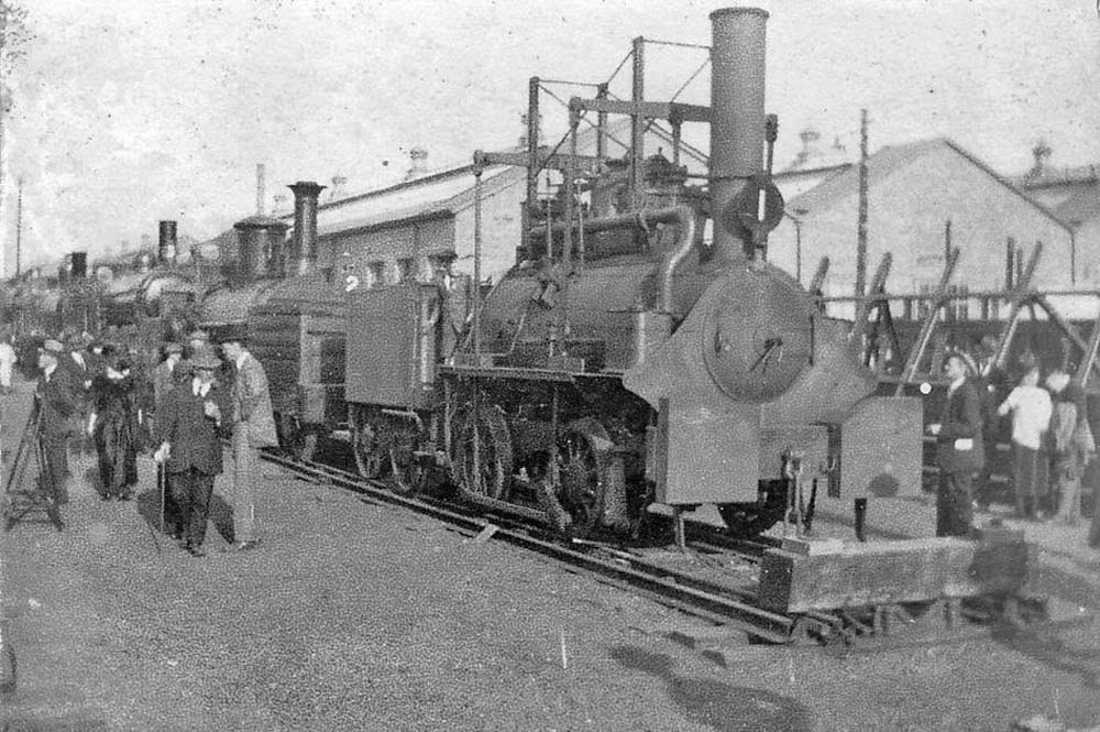 old photo of an old locomotive on the tracks with people looking around it