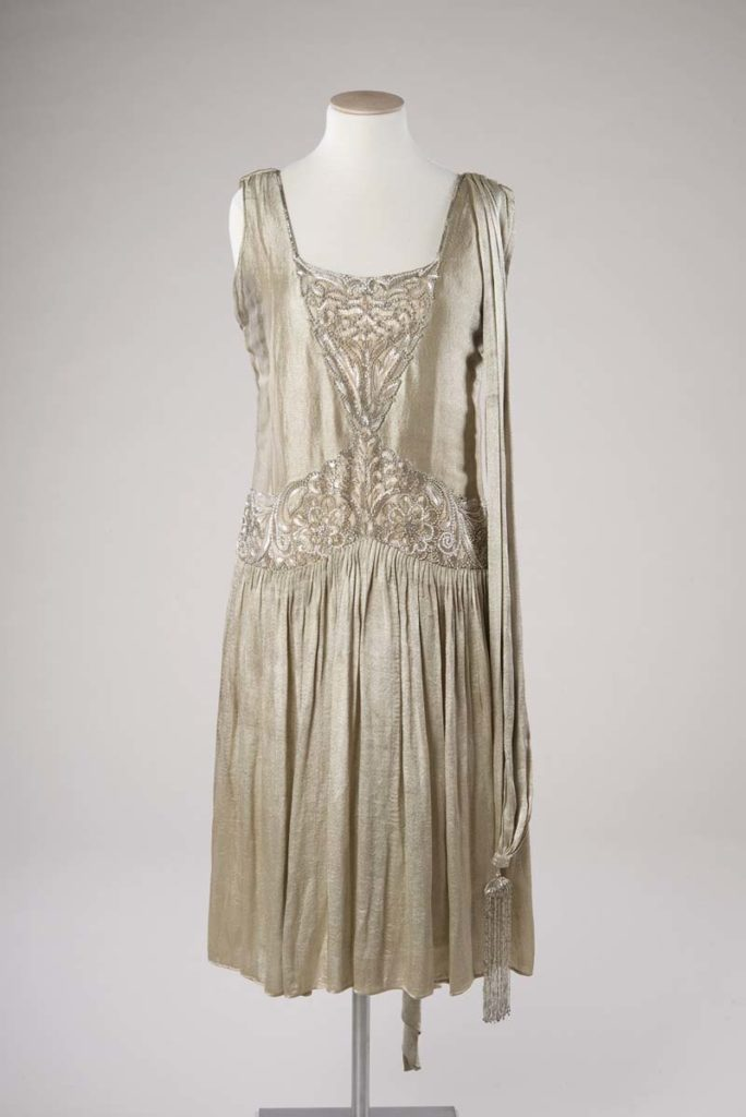 a photo of a 1920s gold lame dress on a mannequin