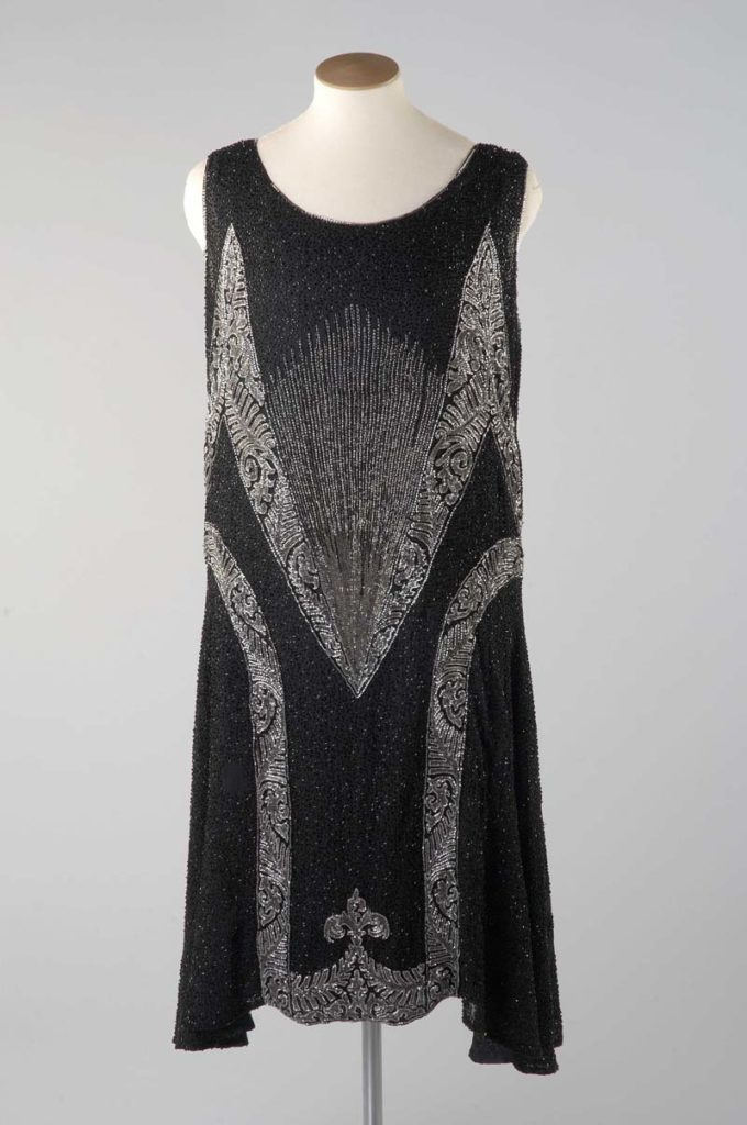 a black silk 1920s styke dress on a mannequin