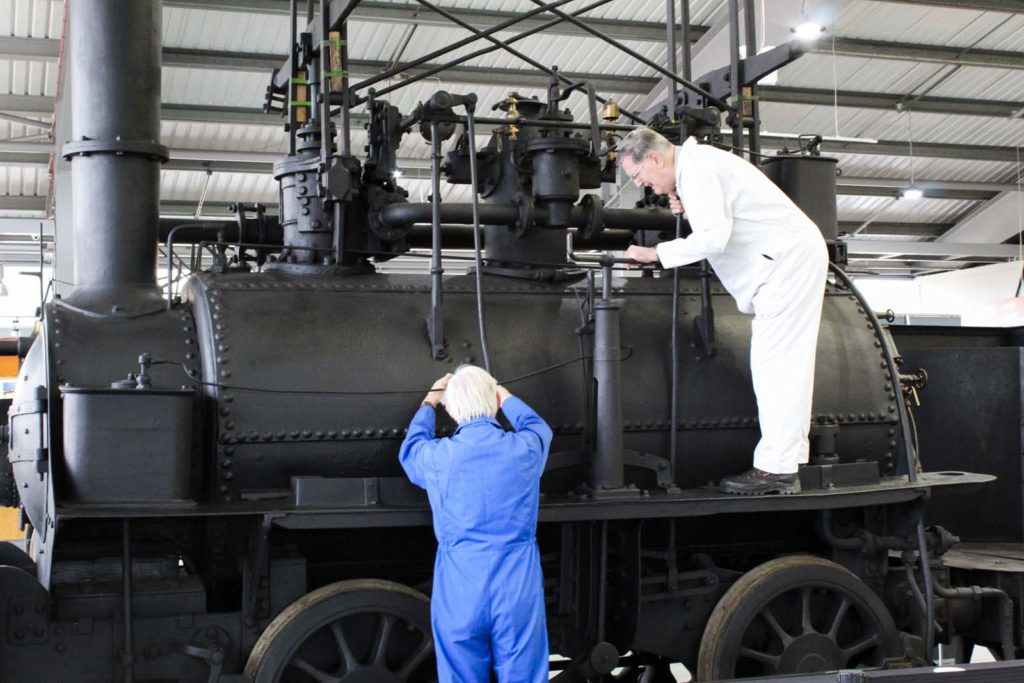 photo of two men in boiler suits working on an old steam locomotive