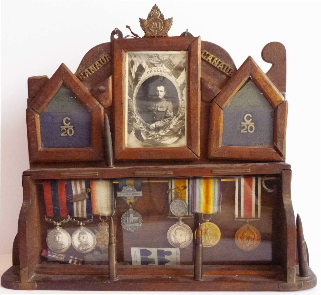 photo of a dispay case made out of wood holding cap badges, photos and medals