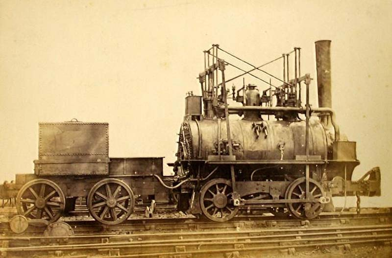 sepia photo of an early locomotive and tender