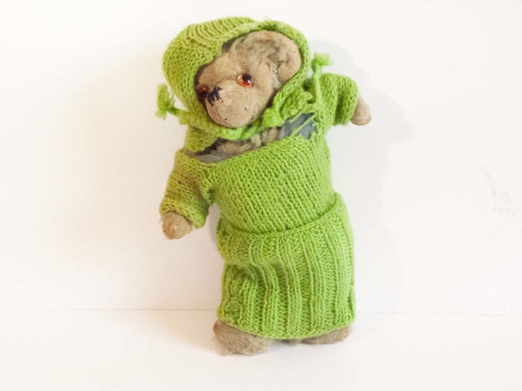 a photo of a teddy bear in a knitted green outfit