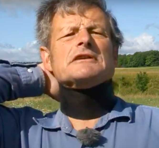 a photo of a very uncomforatble looking man with a leather band round his neck