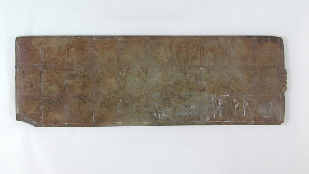 a stone board game with incised squares on it