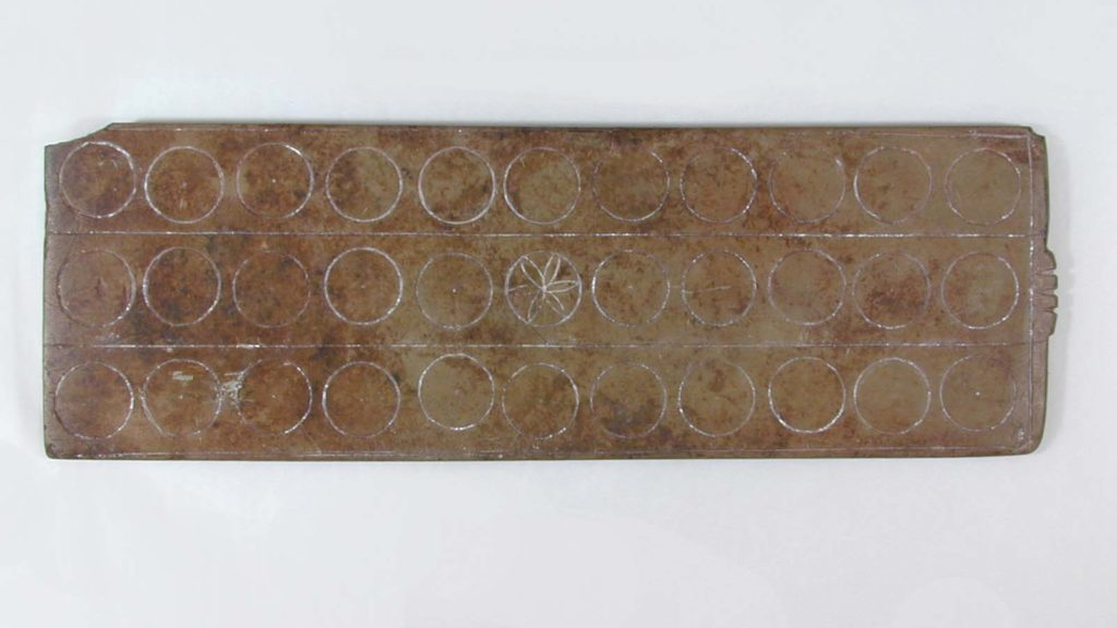 underside of a stone board game with circular designs on it