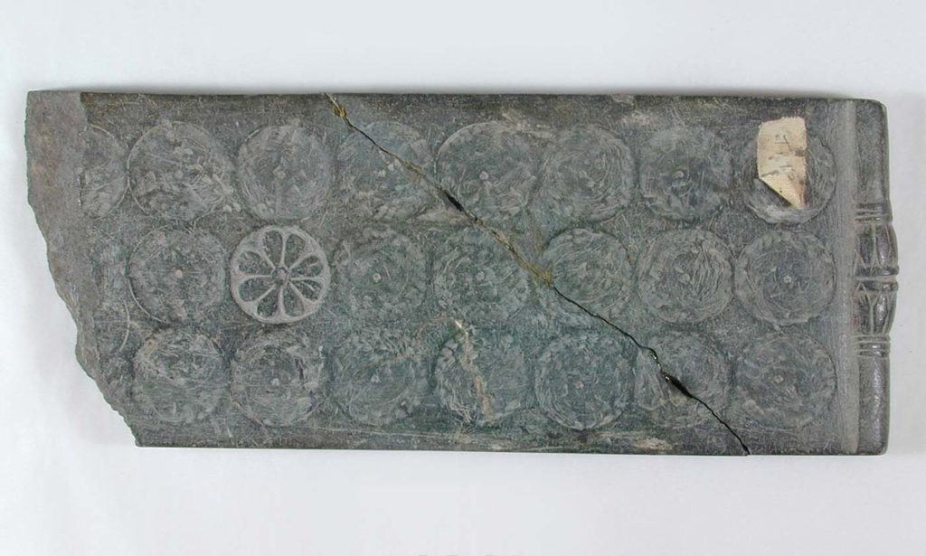 a photo of a stone board game with circular designs on it