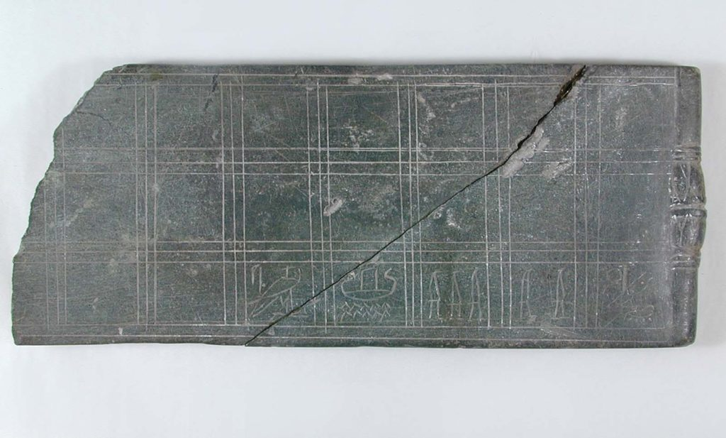 a photo of a stone board game with squares marked on it together with hieroglyphsn it