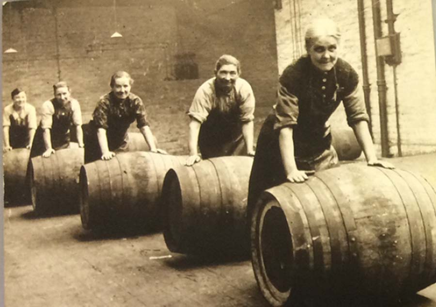 a black and white photo of a group of women rolling beer barrels