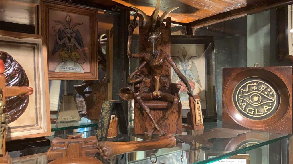 Wooden figurine of Baphomet deity with related objects in museum display case