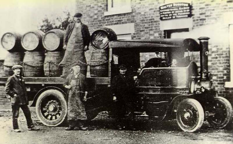 a black and white photo of draymen on thew back of a lorry laden with beer barrels