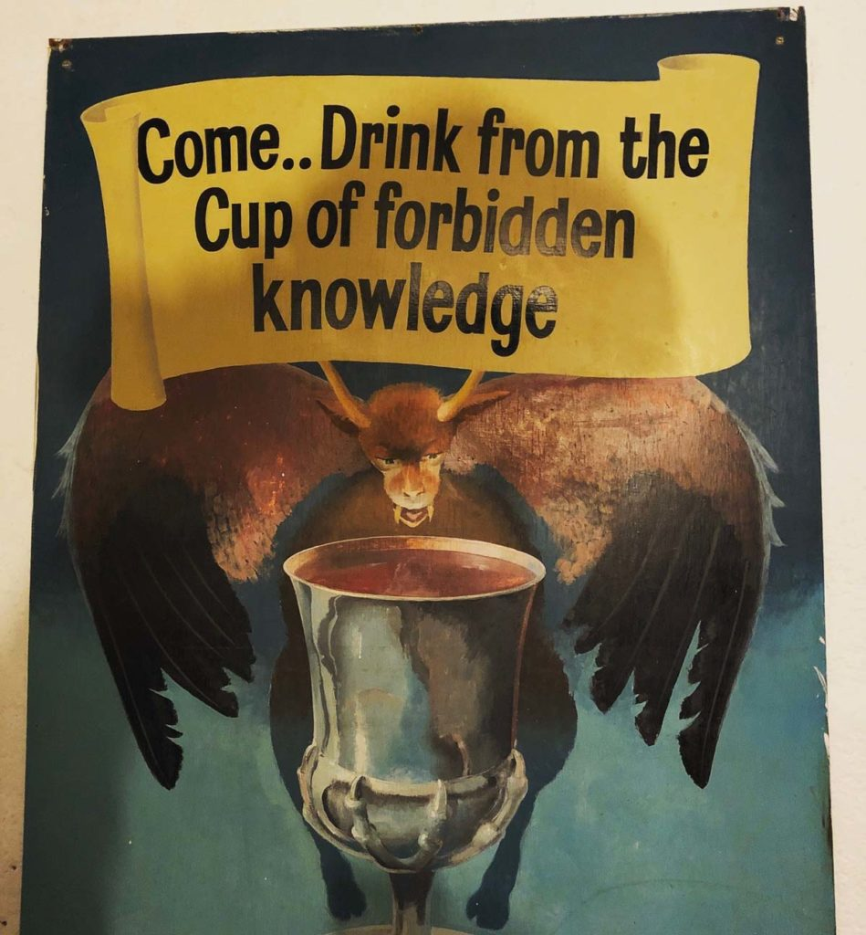a poster with a devil figure drinking from a cauldron