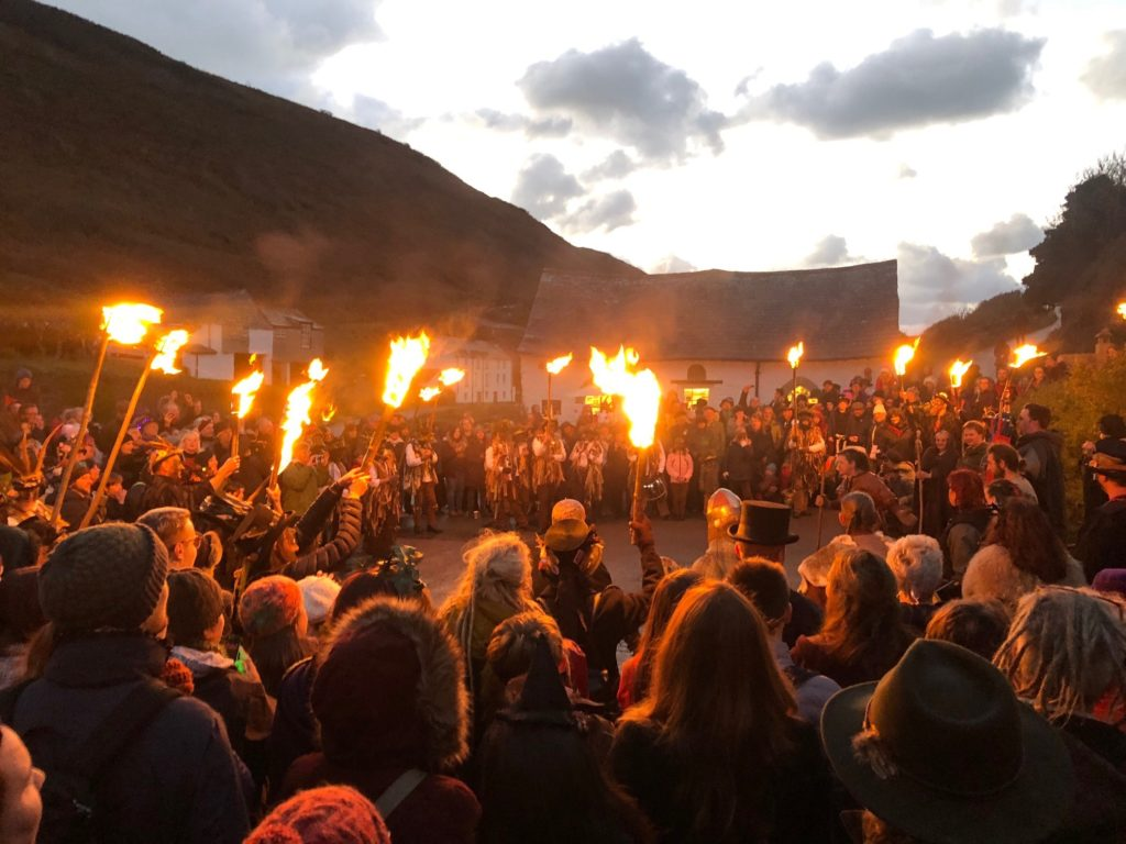 a crowd of people in a cove with torches