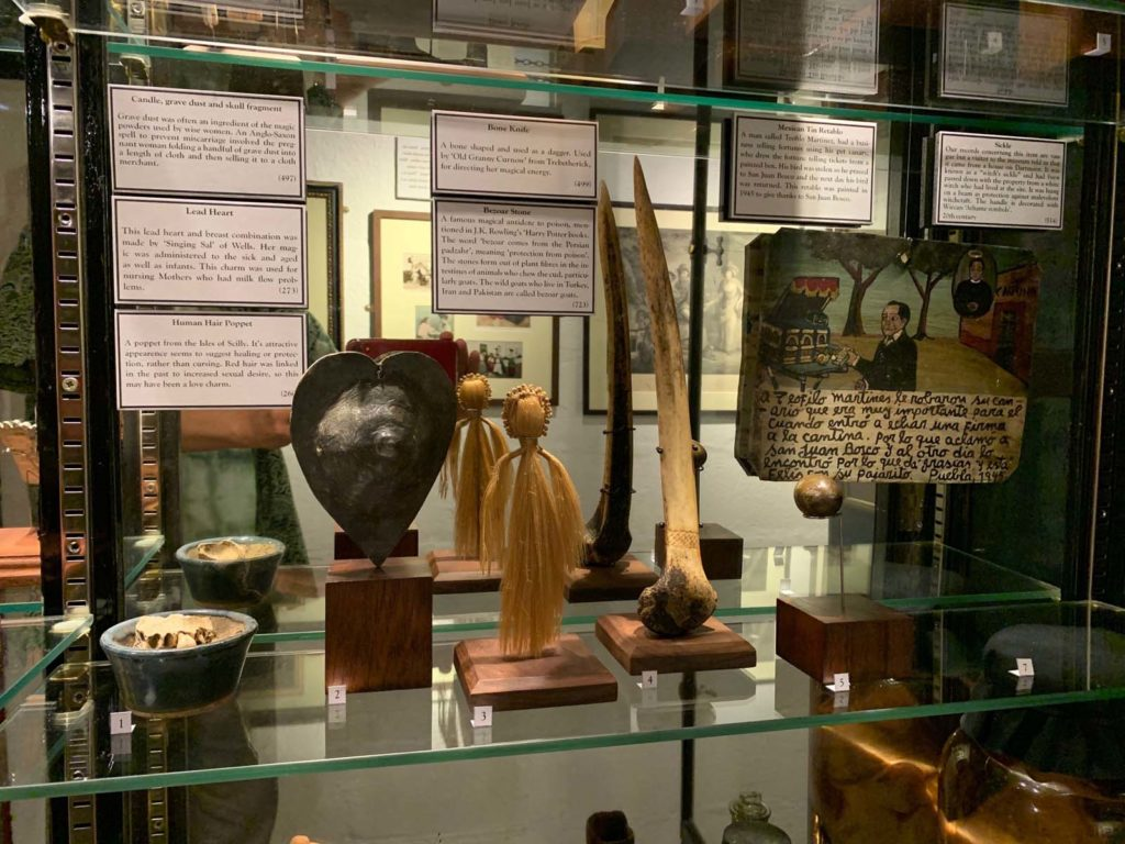A museum display case with a variety of magic themed objects including a lead hart, human hair poppet and bone knife