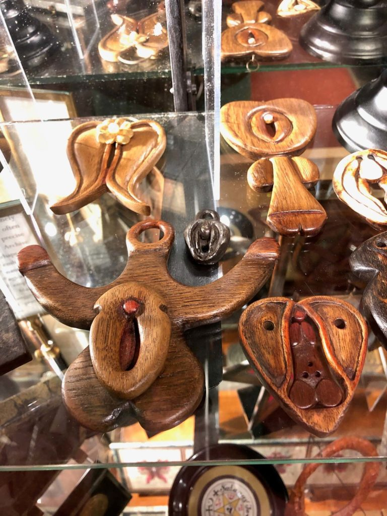 A museum display case containing several wooden phallic and yonic objects